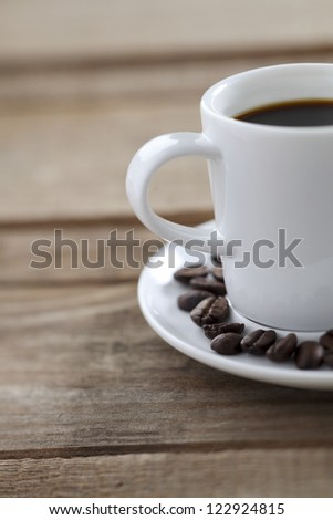 Cup of coffee and a coffee grain on a white saucer
