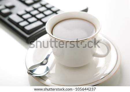 Cup of coffee and a computer keyboard on a white background