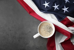 Cup of coffee and American flag on grey background