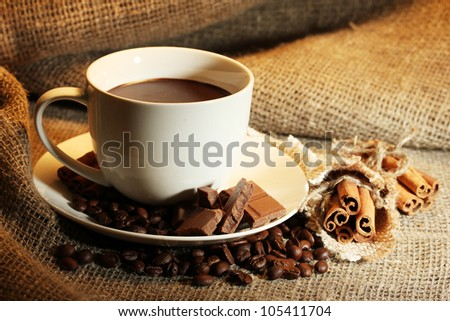 cup of coffee and beans, cinnamon sticks and chocolate on sacking background - stock photo