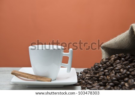 Cup of coffee and beans on an orange vintage background.