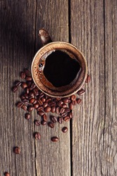 Cup of coffee and beans on vintage wooden background. Top view
