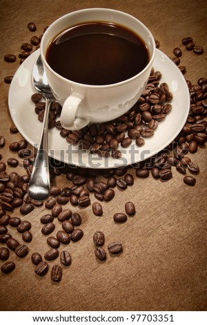 Cup of coffee and beans on wood background