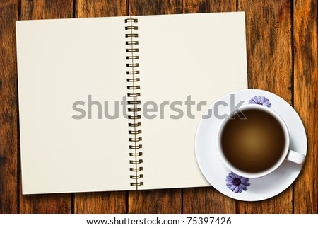 cup of coffee and blank notebook on natural wood texture background
