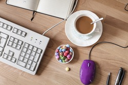 Cup of coffee and bowl with chocolate drops, workplace