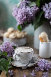 Cup of coffee and cake horns from puff pastry with vanilla cream in a metal box in spring still life with a bouquet of lilacs on a wooden table.