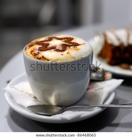 Cup of coffee and cake in cafe, shallow DOF