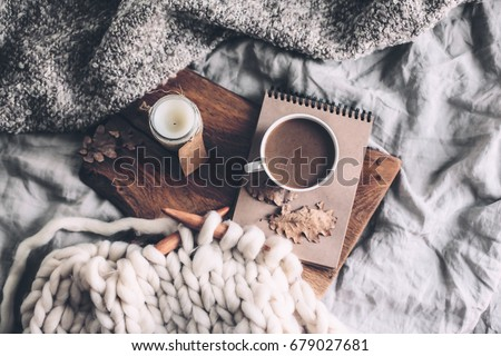 Cup of coffee and candle on rustic wooden serving tray in the cozy bed with blanket. Knitting warm woolen sweater in the autumn weekend, top view.