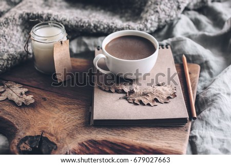 Cup of coffee and candle on rustic wooden serving tray with blanket. Spending autumn weekend in the cozy bed. #679027663