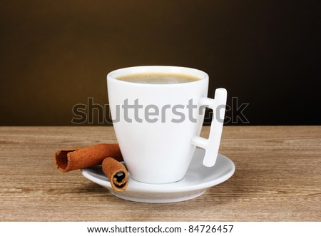 cup of coffee and cinnamon on wooden table on brown background