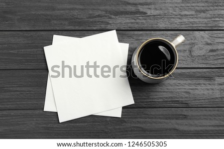 Cup of coffee and clean paper napkins on wooden background, top view