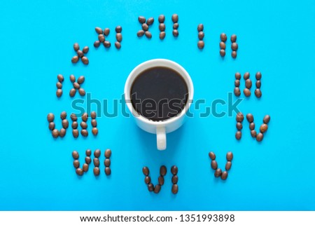 Cup of coffee and clock made of cocoa beans on the blue background.