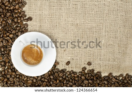 Cup of coffee and coffee beans on burlap