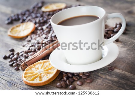 Cup of coffee and coffee beans, warm lighting.