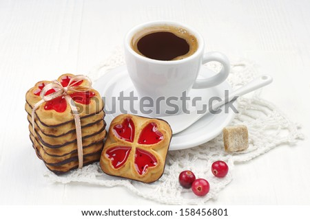 Cup of coffee and cookies with jam tied ribbon and cranberry