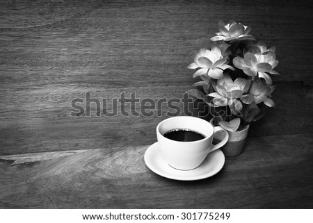 cup of coffee and flower vase on wooden background ,black and white tone