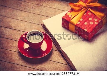 Cup of coffee and gift box with book on a wooden table. Photo in old color image style.