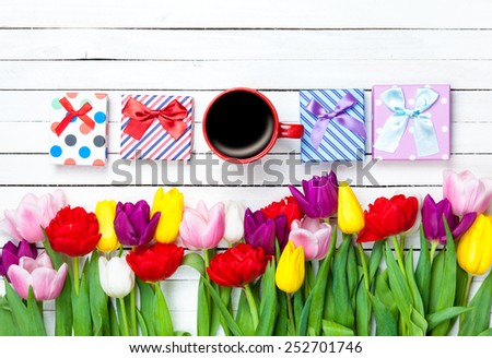 Cup of coffee and gift boxes near flowers on wooden background