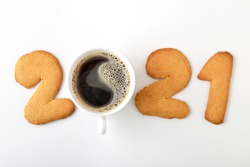 Cup of coffee and gingerbread in the form of the date of the new year - 2021 on a white background.