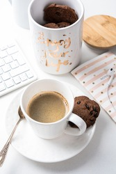 Cup of coffee and jar of chocolate cookies