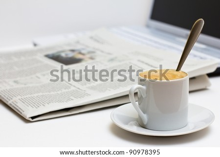 Cup of coffee and newspaper over laptop.