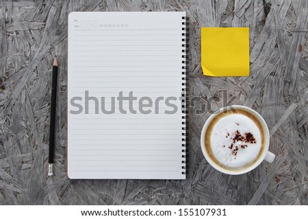 Cup of coffee and notebook paper on a wooden table