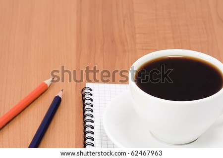 cup of coffee and pens with notepad on table