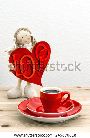 Cup of Coffee and red Valentines Day decoration. Doll girl with LOVE