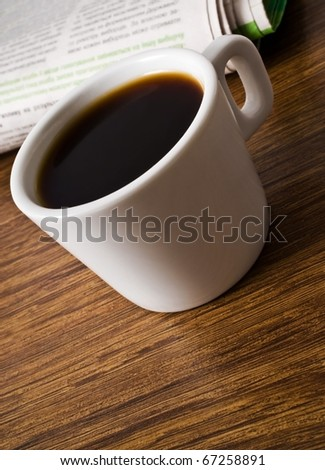 cup of coffee and stack of newspapers closeup