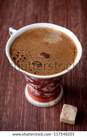Cup of coffee and sugar on vintage board