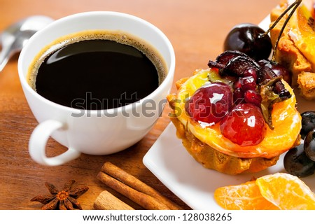 Cup of coffee and sweet fruit cake on a table