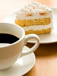 Cup of coffee and tasty cream cake with apricots. Shallow dof.