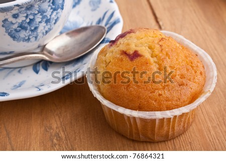 cup of coffee and vanilla muffin with berrie filling on a wooden table