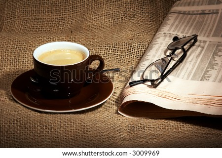 cup of coffee and yellowed newspaper on tattered burlap sack