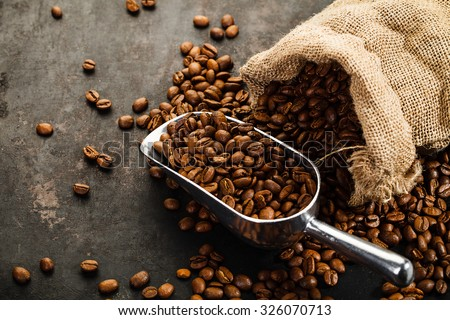 Cup of coffee, bag and scoop on old rusty background - Shutterstock ID 326070713