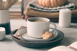 Cup of coffee, books, warm clothes, pumpkin, cookie and candle. Cosy autumn concept.