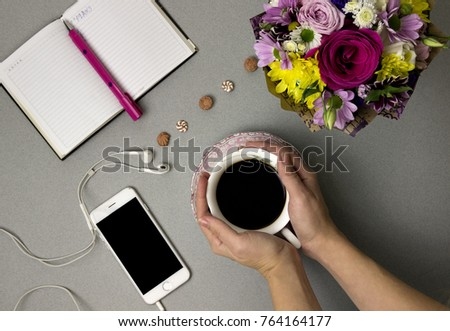 cup of coffee, bouquet of flowers, diary, notebook, pink pen and phone on a gray background, hands holding a cup of coffee