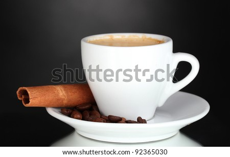 cup of coffee, cinnamon and coffee beans on black background