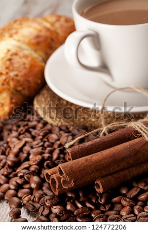 cup of coffee, cinnamon, croissant, over wooden background