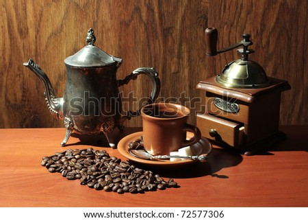 Cup of coffee, coffee pot and grinder over wooden background