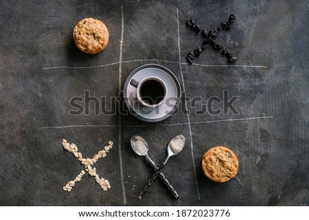 Cup of coffee, cookies, spoons, oatmeal, raisins in the composition and form of tic-tac-toe game on stone background. Tic Tac Toe game. Coffee break concept, top view Foto stock ©