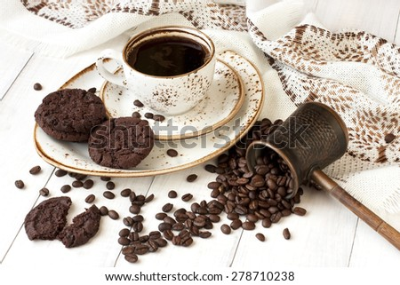 Cup of coffee,  copper turkish coffee pot and coffee beans on wooden background
