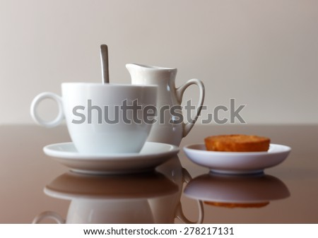 Cup of coffee, creamer jug and muffin on reflective table, side view with selective focus