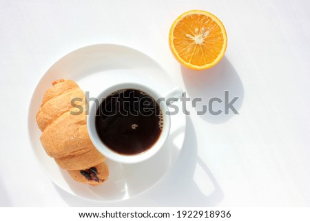 Cup of coffee, croissant and orange on white background. Top view, copy space. Morning espresso on table. Healthy breakfast. Hard light, deep shadow. Selective focus Foto d'archivio ©