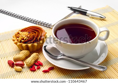 Cup of coffee, cupcake, notebook and pen