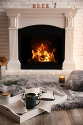 Cup of coffee, glasses and book on tray near fireplace indoors. Cozy atmosphere