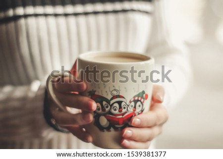 cup of coffee in female hands, cup with Christmas pattern, picture with penguins on cup, festive tableware, Christmas cup