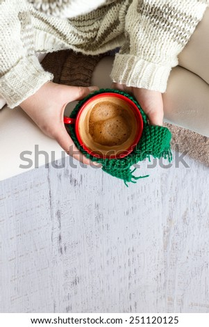 Cup of coffee in female hands, top view