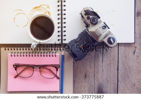 Cup of coffee in morning with old camera and note book on Wood Background