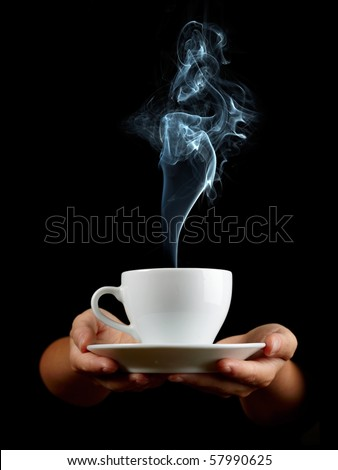 Cup of coffee in the women\'s hand on black background